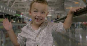 Weinig kind die bij vlakke roltrap en het stellen berijden stock video