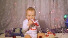 Weinig kind die een Kerstmisstuk speelgoed met een sneeuwman spelen dichtbij de Kerstboom stock footage