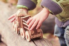 Weinig kind die een kinderen` s stuk speelgoed trein in het park spelen Stock Afbeeldingen