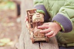 Weinig kind die een kinderen` s stuk speelgoed trein in het park spelen Stock Afbeelding
