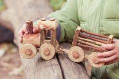 Weinig kind die een kinderen` s stuk speelgoed trein in het park spelen Stock Foto