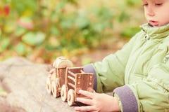 Weinig kind die een kinderen` s stuk speelgoed trein in het park spelen Royalty-vrije Stock Afbeeldingen