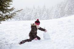 Weinig kind die een sneeuwman bouwen Stock Afbeelding