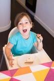 Weinig kind die gezicht van de cake het grappige uitdrukking eten Stock Foto