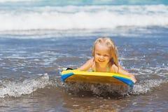 Weinig kind die met bodyboard op de overzeese golven zwemmen Royalty-vrije Stock Foto's