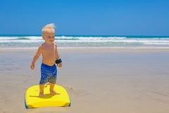 Weinig kind die met bodyboard op het overzeese zandstrand zwemmen Stock Foto