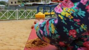 Weinig kind die met vormen in de zandbak op de speelplaats spelen stock video