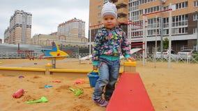 Weinig kind die met vormen in de zandbak op de speelplaats spelen stock videobeelden
