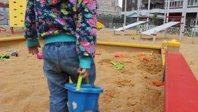 Weinig kind die met vormen in de zandbak op de speelplaats spelen stock footage