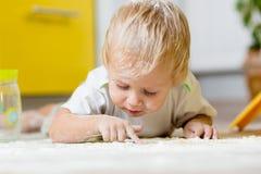 Weinig kind die op zeer slordige keukenvloer leggen royalty-vrije stock afbeeldingen