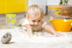 Weinig kind die op zeer slordige keukenvloer leggen royalty-vrije stock afbeelding