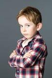 Weinig kind die zich van profiel bevinden die zijn teleurstelling of schande uitdrukken stock foto's