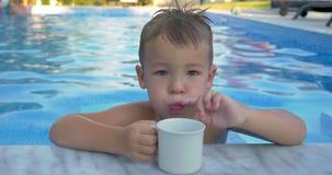 Weinig kind drinkwater in het zwembad stock footage