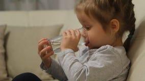 Weinig kind drinkwater van een glaszitting op een bank in de ruimte stock footage