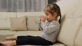 Weinig kind drinkwater van een glaszitting op een bank in de ruimte stock videobeelden