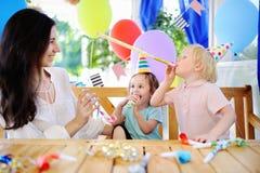 Weinig kind en hun moeder vieren verjaardagspartij met kleurrijke decoratie en cakes met kleurrijke decoratie en cake Stock Foto