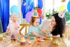 Weinig kind en hun moeder vieren verjaardagspartij met kleurrijke decoratie en cakes met kleurrijke decoratie en cake Stock Afbeeldingen