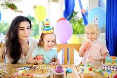 Weinig kind en hun moeder vieren verjaardagspartij met kleurrijke decoratie en cakes met kleurrijke decoratie en cake Royalty-vrije Stock Fotografie