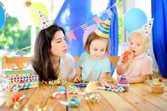 Weinig kind en hun moeder vieren verjaardagspartij met kleurrijke decoratie en cakes met kleurrijke decoratie en cake Royalty-vrije Stock Foto