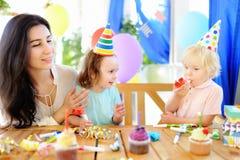 Weinig kind en hun moeder vieren verjaardagspartij met kleurrijke decoratie en cakes met kleurrijke decoratie en cake Stock Fotografie
