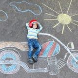 Weinig kind in helm met de tekening van het motorfietsbeeld met colo Stock Foto