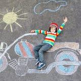 Weinig kind in helm met de tekening van het motorfietsbeeld met colo Stock Afbeeldingen