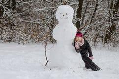 Weinig kind het stellen met reusachtige sneeuwman Stock Foto