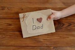 Weinig kind houdt een kaart I liefdepapa De prentbriefkaar van karton en verpakkend die document wordt gemaakt, met houten hart w Royalty-vrije Stock Foto's