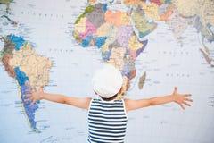 Weinig kind in kapiteinshoed het uitspreiden handen aan wereldkaart vóór reis stock afbeeldingen