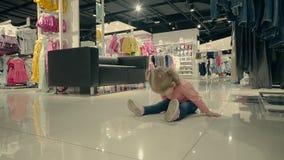 Weinig kind in kledingsopslag zit op de vloer en de lach, langzame motie stock footage