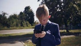 Weinig kind in kostuum, een kleine zakenman die met een mobiele telefoon, pret spelen stock footage