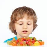 Weinig kind met gekleurd geleisuikergoed op witte achtergrond royalty-vrije stock foto