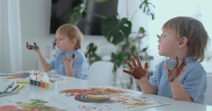Weinig kind met handen schilderde in kleurrijke verven klaar voor handdrukken stock video