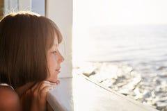 Weinig kind met kort donker haar, die uit van dek van schip, het bewonderen kalme overzees kijken terwijl het rusten tijdens haar stock fotografie
