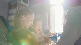 Weinig kind met mama als de stomatologievoorzitter - het meisje glimlacht stock video