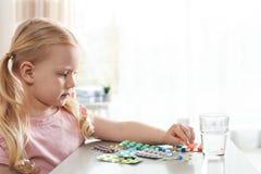 Weinig kind met vele verschillende pillen bij lijst Gevaar van geneesmiddelintoxicatie royalty-vrije stock foto's