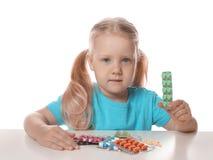 Weinig kind met vele verschillende pillen op wit Gevaar van geneesmiddelintoxicatie royalty-vrije stock fotografie