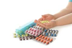 Weinig kind met vele verschillende pillen op witte achtergrond Gevaar van geneesmiddelintoxicatie royalty-vrije stock foto