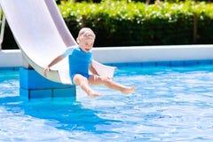 Weinig kind op waterdia in zwembad Royalty-vrije Stock Afbeeldingen