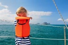 Weinig kind in reddingsvest aan boord van varende boot Royalty-vrije Stock Foto's