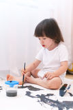 Weinig kind schildert thuis met borstel en gouache Royalty-vrije Stock Afbeelding