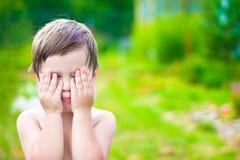 Weinig kind speelt huid-en-zoekt verbergend gezicht stock foto's