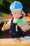 Weinig kind speelt in zandbak Stock Foto's