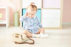 Weinig kind in studio het spelen met de telefoon stock afbeelding