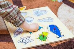 Weinig kind zet het eenvoudige raadsel op de vloer Stock Foto's