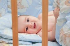 Weinig kindbaby die in bed glimlachen stock foto