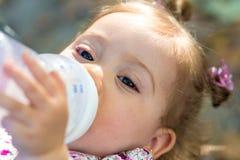 Weinig kindconsumptiemelk van zuigfles in openlucht stock foto's
