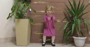 Weinig kinddans dichtbij bloempotten en houten omheining Voel gelukkig, het glimlachen stock footage