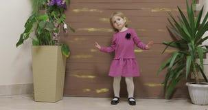 Weinig kinddans dichtbij bloempotten en houten omheining Voel gelukkig, het glimlachen stock videobeelden