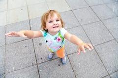 Weinig kindglimlach en trekt haar handen naar camera Stock Fotografie